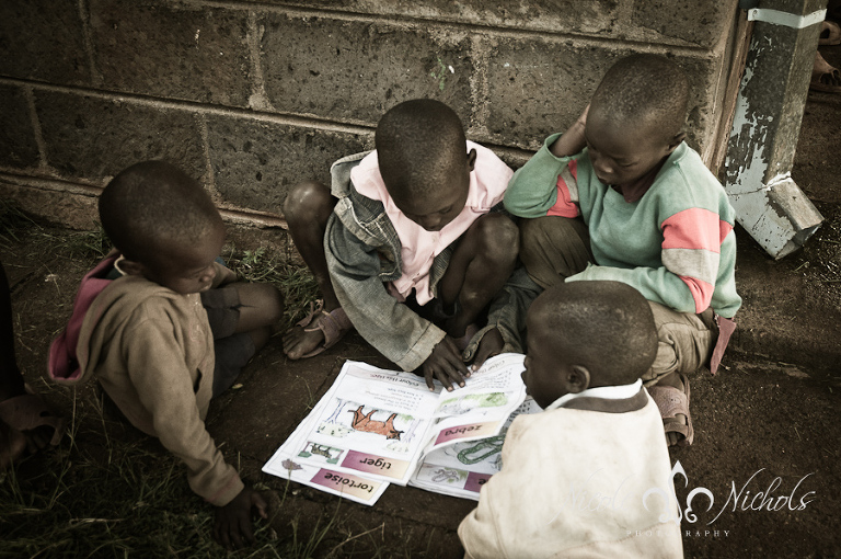 kids at a Kenyan orphanage share an educational book excited to learn the names of animals