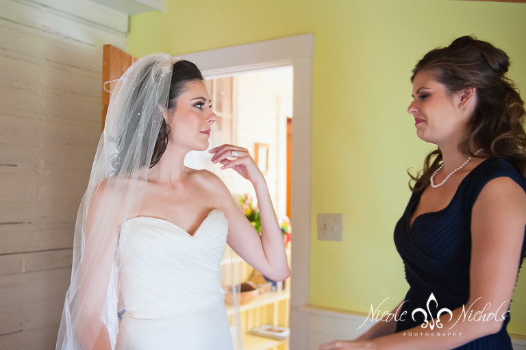 The Bride's sister helps her get ready to walk down the aisle